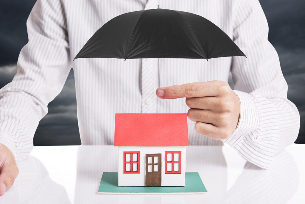 Man holding umbrella above house model